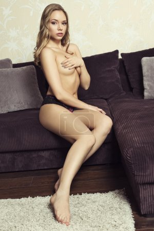 nude woman sitting on couch