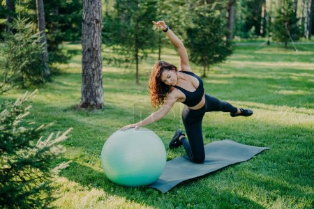 Photo pour Flexible active woman in sportsclothes makes fitness exercises on karemat with fitball, raises arms and breathes fresh air in forest has morning workout poses over nature background. Healthy lifestyle - image libre de droit