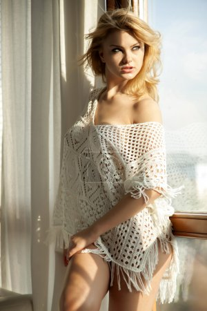 Young slim sexy woman in brown sweater against the window