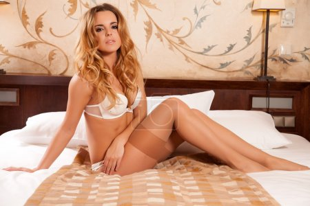 Photo for Beautiful and sexy young adult attractive sensuality pretty blonde babe woman in white lingerie on the bed in bedroom on luxury style exclisive hotel apartment - Royalty Free Image