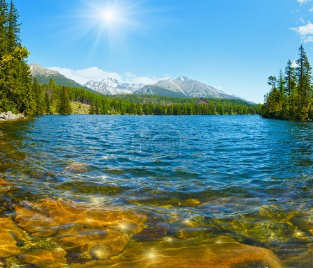 Photo for Mountain lake Strbske Pleso (Slovakia) spring view with sunshine in blue sky. - Royalty Free Image