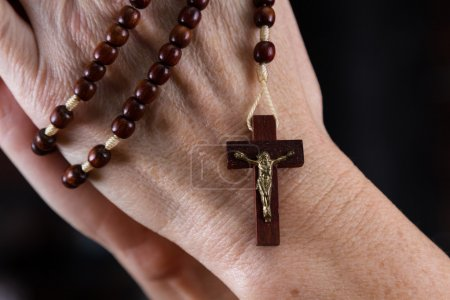 Photo for Close up of a woman's hands holding rosary beads focused on the cross - Royalty Free Image