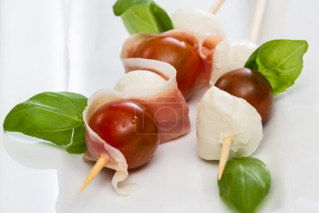 Photo for Close up of a fresh mozzarella and tomato appetizer with basil and proscuitto on a white plate - Royalty Free Image