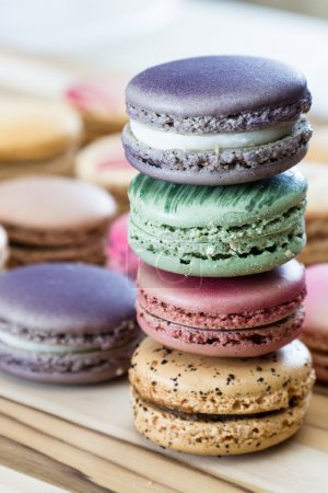 Photo for Classic french macaroons hand made and decorated in a variety of colors on a wooden table - Royalty Free Image