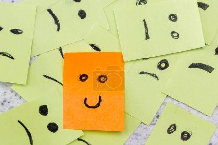 Photo pour Concept pour une attitude positive avec de petites notes de bureau aux multiples visages et qui se démarque avec un sourire - image libre de droit