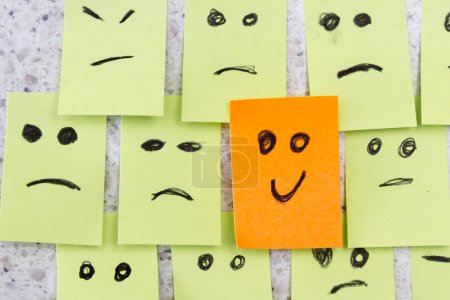 Photo for Concept for a positive attitude with small office notes with multiple faces and one that stands out with a smile - Royalty Free Image