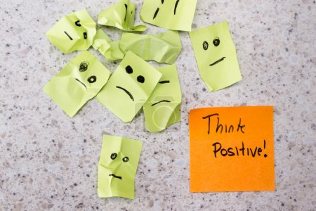 Photo for Concept for a positive attitude with small crumbled up sad faces and a note with the phrase think positive - Royalty Free Image