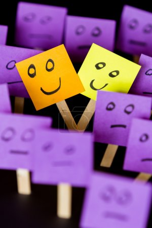 Photo for Concept for being different and being happy in a word of normal, hand drawn faces on sticky notes over a black background - Royalty Free Image