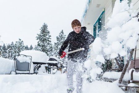 young boy shoveling snow