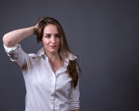 Young woman wearing white shirt holding collar up....