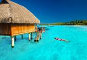 Young woman swimming in tropical lagoon next to overwater villa