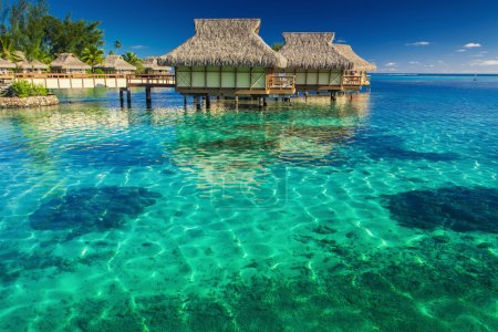 Villas in the lagoon into shallow water with coral