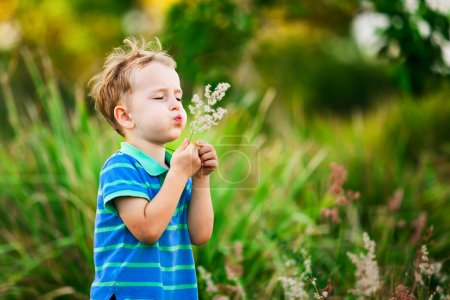 Boy blowing on a dandelion in the park