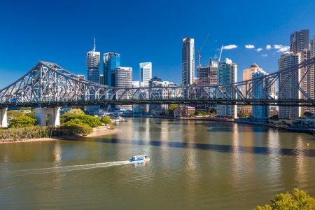 Ferry boat under Story Bridge with skyline of Brisbane
