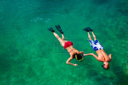 couple snorkeling in clean water over coral reef