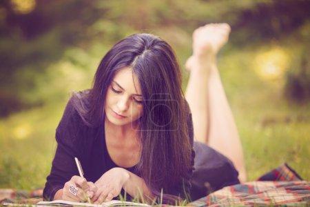 Photo pour Belle femme écrivain est inspiré par la nature - image libre de droit