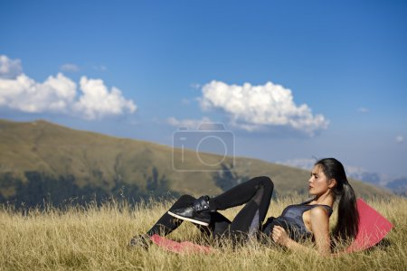 Exercising fitness woman doing exercises in nature. Girl doing m