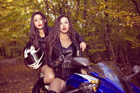 Two beautiful women passionate about motorcycles, posing in natu