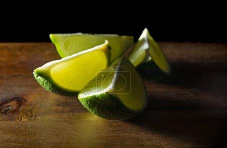 Quartered lime fruit in dark wooden surface...