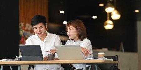 Foto de Foto del equipo de administradores del sitio web que trabaja con la tableta y el ordenador portátil mientras están sentados juntos - Imagen libre de derechos