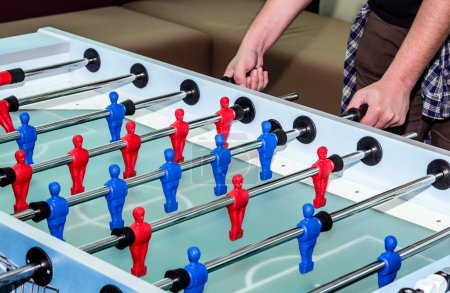 caucasian male playing table soccer football game