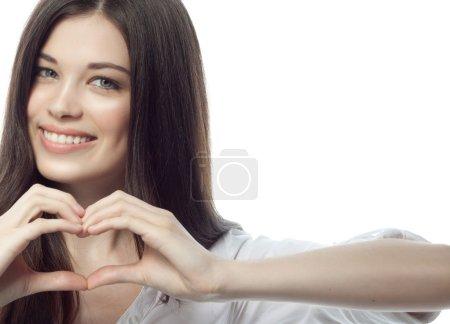 Photo pour Gros plan portrait de attrayant caucasien souriant femme brune isolé sur blanc studio shot lèvres dent sourire visage cheveux tête et épaules regarder caméra dent femme d'affaires coeur - image libre de droit