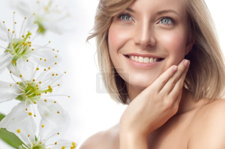 Photo for Closeup portrait of attractive  caucasian smiling woman blond isolated on white studio shot lips toothy smile face hair head and shoulders looking up blue eyes tooth flowers spring aroma - Royalty Free Image