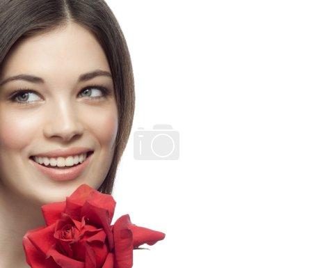 Photo pour Gros plan portrait de attrayant caucasien souriant femme brune isolé sur blanc studio shot lèvres dent sourire visage cheveux tête et épaules dent rouge rose fleur - image libre de droit