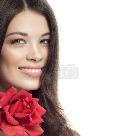 Photo pour Closeup portrait d'attrayant caucasien souriante brunette femme isolé sur studio blanc tourné lèvres pleines dents sourire visage cheveux tête et les épaules, regardant fleur rose de dent rouge appareil photo - image libre de droit