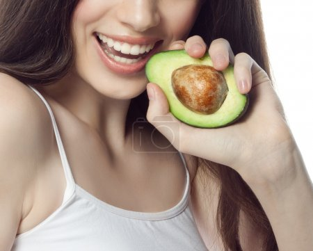 Photo for Portrait of attractive  caucasian smiling woman isolated on white studio shot eating avocado - Royalty Free Image