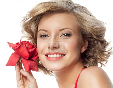 Photo for Closeup portrait of attractive  caucasian smiling woman blond isolated on white studio shot lips toothy smile face hair head and shoulders looking at camera blue eyes tooth red rose flower - Royalty Free Image