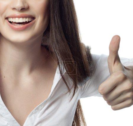 Photo pour Closeup portrait d'attrayant caucasien souriante brunette femme isolé sur blanc studio tourné les lèvres pleines dents sourire visage cheveux tête et des épaules dent mains pouces vers le haut de femme d'affaires ok - image libre de droit