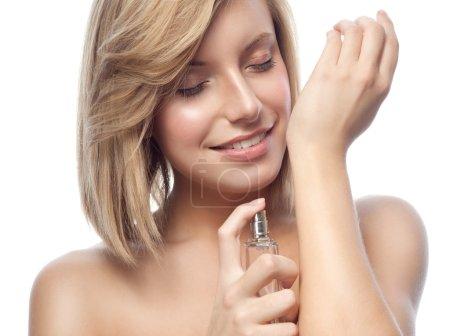 Photo pour Portrait de la belle jeune femme souriante caucasienne isolée sur blanc studio shot appliquant parfum beauté de visage closeup - image libre de droit