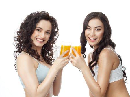 Photo pour Closeup portrait de deux attrayant caucasien et asiatique souriante brunette femmes isolées sur studio blanc tourné lèvres pleines dents sourire visage cheveux tête et épaules, regardant dent caméra boire le jus d'orange - image libre de droit