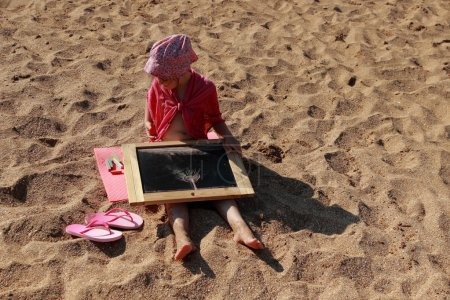 little girl sitting on the beach and drawing