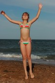 Happy little girl in a swimsuit is played on sand near the Black Sea and relaxing, East Crimea, Ukraine