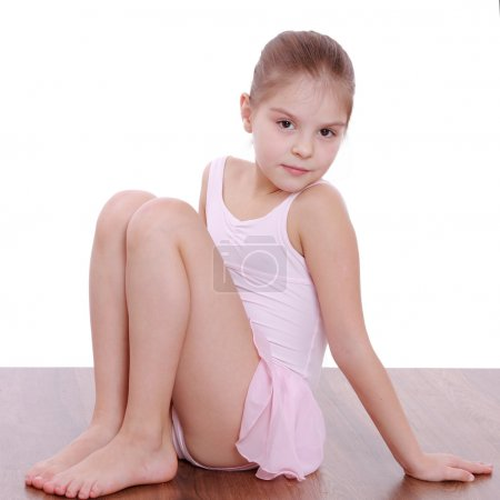 Photo for Studio image of a beautiful little girl in a pink leotard doing gymnastic exercises on the floor - Royalty Free Image