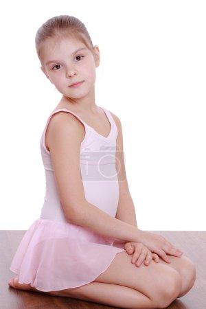 Photo pour Studio image d'une belle petite fille dans un justaucorps rose faisant des exercices de gymnastique sur le sol - image libre de droit