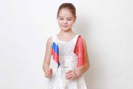 Photo pour Fière petite fille tenant un drapeau national de la Fédération de Russie (Russie) et de la bannière de victoire - drapeau d'assaut de la 150e ordre de Koutouzov Ii degré Idritsa Division d'infanterie dans la seconde guerre mondiale - image libre de droit