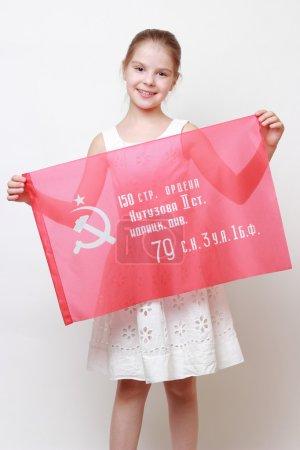 Photo pour Patriotique petite fille tenant la bannière de la victoire - drapeau d'assaut de la 150e ordre de Koutouzov Ii degré Idritsa Division d'infanterie dans la seconde guerre mondiale - image libre de droit