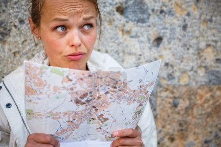 Female tourist with a map discovering a foreign city