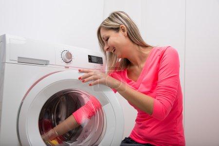 woman doing laundry at washing machine
