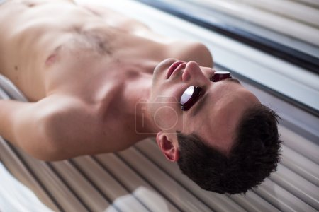 Handsome young man relaxing during a tanning session in a solarium
