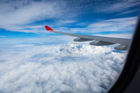 Photo pour Vue spectaculaire depuis la fenêtre de l'avion, offrant une vue magnifique nuages et ciel bleu lors d'un voyage rapide - image libre de droit
