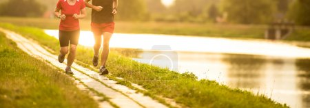 Photo for Couple running outdoors, at sunset, by a river, staying active and fit - Royalty Free Image