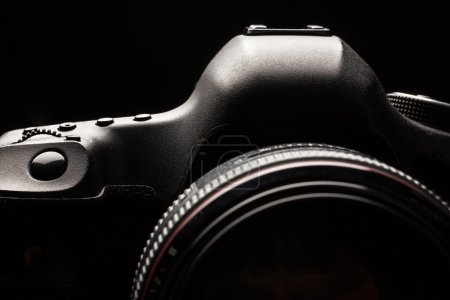 Photo for Professional modern DSLR camera low key image - Modern DSLR camera with a very wide aperture lens on - Royalty Free Image