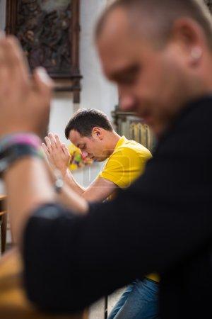 Photo pour Beau jeune homme priant dans une église à genoux - image libre de droit