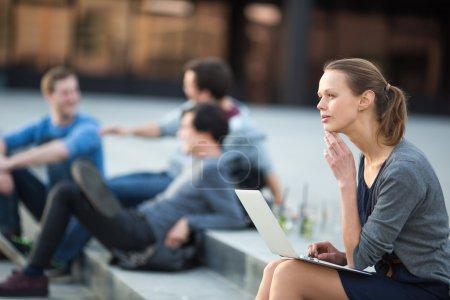 Photo pour Portrait d'une jeune femme élégante, utilisant un ordinateur portable, étant coûteuse dans un contexte urbain ou urbain (DOF peu profond, image couleur tonique ) - image libre de droit