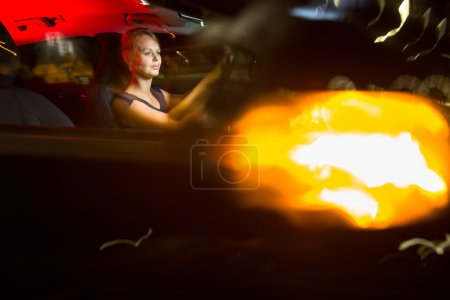 Woman driving a car at night
