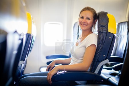 Photo pour Pretty, young female passenger on board of an aircraft while on the flight - image libre de droit